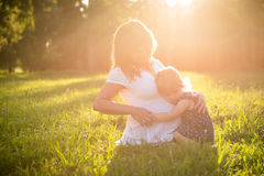 Pregnant woman with child in nature Stock Images