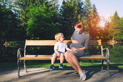 Pregnant woman with child on nature. Royalty Free Stock Image