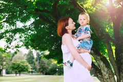 Pregnant woman with child outdoors. Pregnant women with child outdoors. Mother and son on nature in park. Little child boy is sitting on belly of his mother Stock Photos