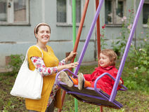 Pregnant  woman with child on swing Stock Photo