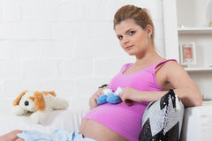 Pregnant  woman with children's clothes. Stock Photo