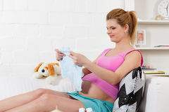 Pregnant  woman with children's clothes. Royalty Free Stock Photography