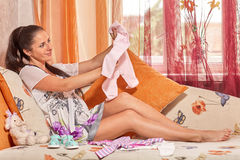 Pregnant  woman with children's clothes. Royalty Free Stock Photos