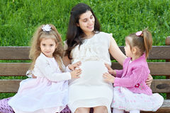 Pregnant woman and children in summer city park outdoor, happy family, bright sunny day and green grass, beautiful people portrait Stock Photography