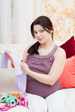 Pregnant woman chooses children's things Stock Images