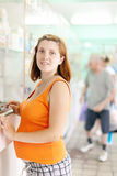 Pregnant woman chooses drugs at  pharmacy Stock Photography