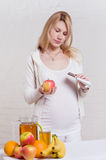 Pregnant woman choosing between apple and chocolate Stock Photo