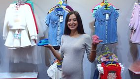 Pregnant woman choosing Baby clothing in baby and maternity shop.