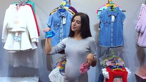 Pregnant woman choosing Baby clothing in baby shop