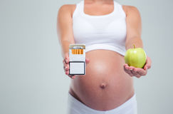 Pregnant woman choosing beetwin cigarettes and apple Royalty Free Stock Photography