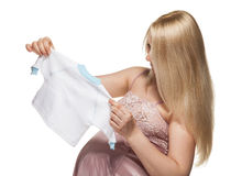 Pregnant woman choosing clothes for newborn Stock Photos