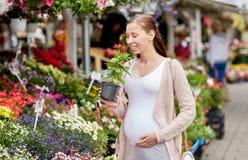 Pregnant woman choosing flowers at street market Royalty Free Stock Image