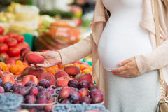 Pregnant woman choosing fruits at street market Royalty Free Stock Images