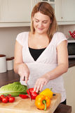 Pregnant Woman Chopping Up Fresh Vegetables Royalty Free Stock Images
