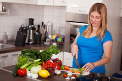 Pregnant Woman Chopping Up Fresh Vegetables Royalty Free Stock Photo