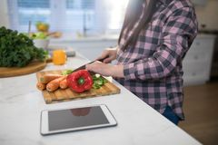 Pregnant woman chopping vegetables in kitchen. Mid section of pregnant woman chopping vegetables in kitchen Royalty Free Stock Image