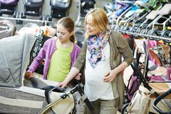 Pregnant woman chosing pram Royalty Free Stock Images