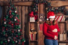 A pregnant woman in a Christmas costume is stroking her belly. A pregnant woman in a Christmas costume is stroking her belly stock photography