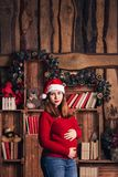 A pregnant woman in a Christmas costume is stroking her belly. A pregnant woman in a Christmas costume is stroking her belly stock images