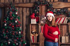 A pregnant woman in a Christmas costume is stroking her belly. A pregnant woman in a Christmas costume is stroking her belly royalty free stock photos