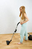 Pregnant woman cleaning floor with vacuum cleaner royalty free stock images