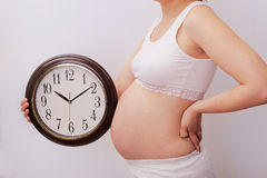 Pregnant woman with clock Royalty Free Stock Photography