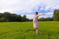 Pregnant woman with closed eyes and open hands Stock Photo