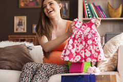 Pregnant woman with clothes for baby Stock Photo