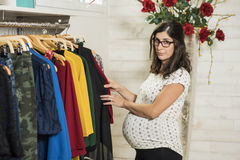Pregnant woman in clothes store looking some clothes Stock Image