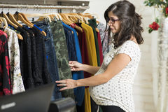 Pregnant woman in clothes store looking some clothes Royalty Free Stock Photos