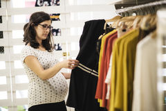 Pregnant woman in clothes store looking some clothes Royalty Free Stock Photo