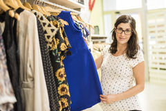 Pregnant woman in clothes store looking some clothes Stock Images