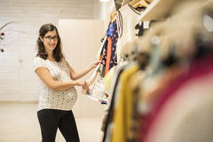 Pregnant woman in clothes store looking some clothes Royalty Free Stock Photography