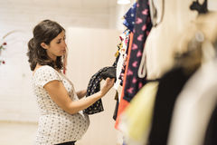 Pregnant woman in clothes store looking some clothes Royalty Free Stock Images
