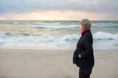 Pregnant woman in a coat walks by the sea Royalty Free Stock Photos