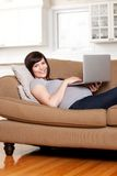Pregnant Woman with Computer. Happy pregnant woman using computer in living room Stock Photos