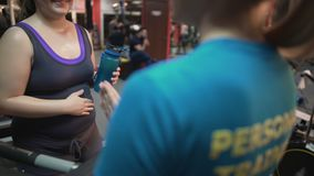Pregnant woman consulting with personal trainer on pregnancy exercises in gym. Stock footage stock footage