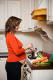 Pregnant woman cooking Royalty Free Stock Photo