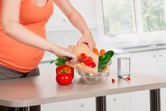 Pregnant woman cooking at kitchen Stock Image