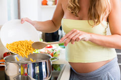 Pregnant woman cooking pasta in domestic kitchen Stock Images