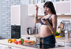 Pregnant woman cooking, reading recipe from your phone Royalty Free Stock Images
