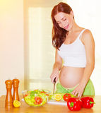 Pregnant woman cooking salad Stock Photography