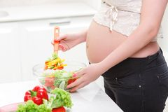 Pregnant woman cooking salad Stock Images