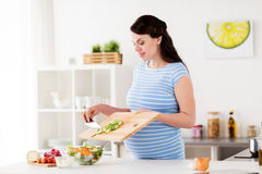 Pregnant woman cooking vegetable salad at home Royalty Free Stock Images