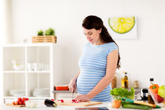 Pregnant woman cooking vegetables at home Stock Photography