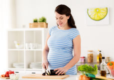 Pregnant woman cooking vegetables at home Stock Images