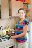 Pregnant woman cooks in the pan Royalty Free Stock Photos