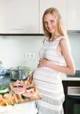 Pregnant woman cooks salmon Stock Photo