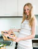 Pregnant woman cooks salmon Stock Photos