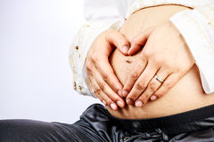 Pregnant woman creating heart shape with her hand Stock Images